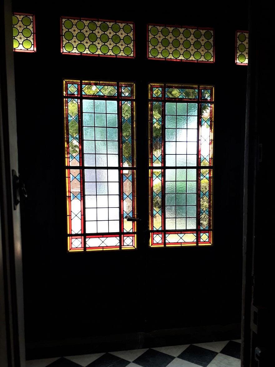 Double porte d'entrée et imposte ornées de vitraux géométriques